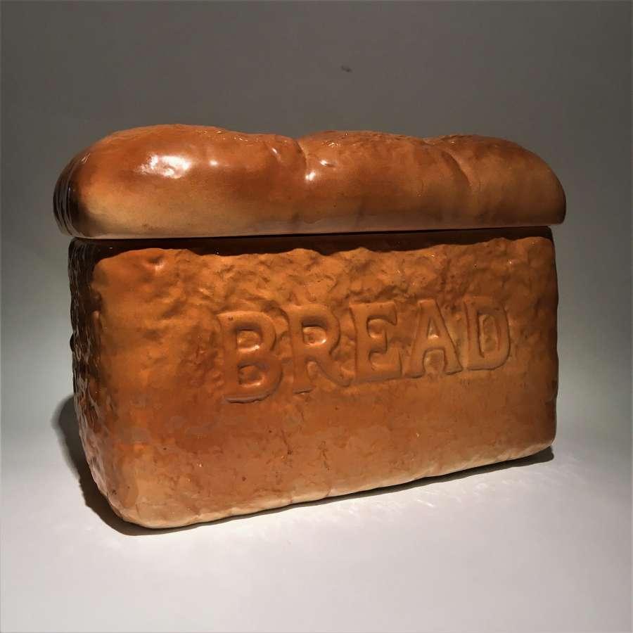 A trompe l'oeil pottery bread bin shaped like a loaf of bread