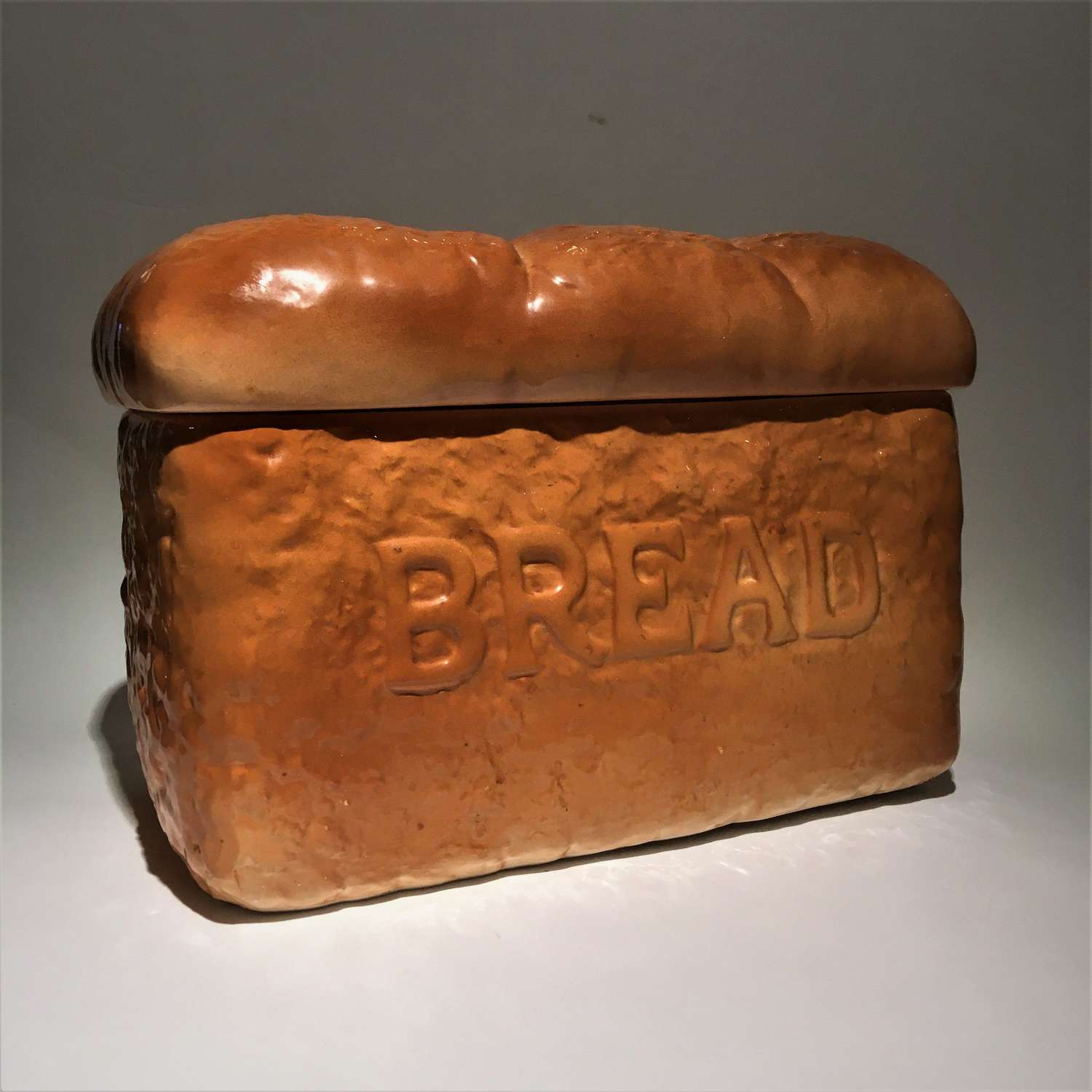 A trompe l'oeil pottery bread bin shaped like a loaf of bread